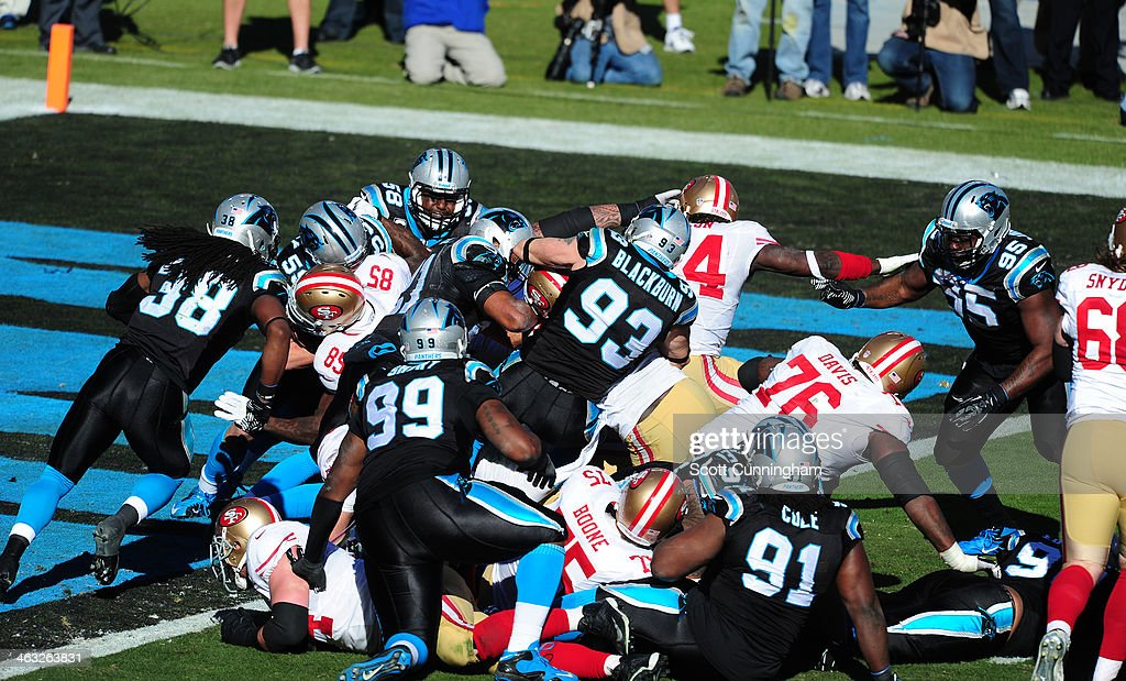 Frank Gore of the San Francisco 49ers is tackled during the NFC Divisional Playoff Game by Chase Blackburn and Mike Mitchell of the Carolina Panthers...