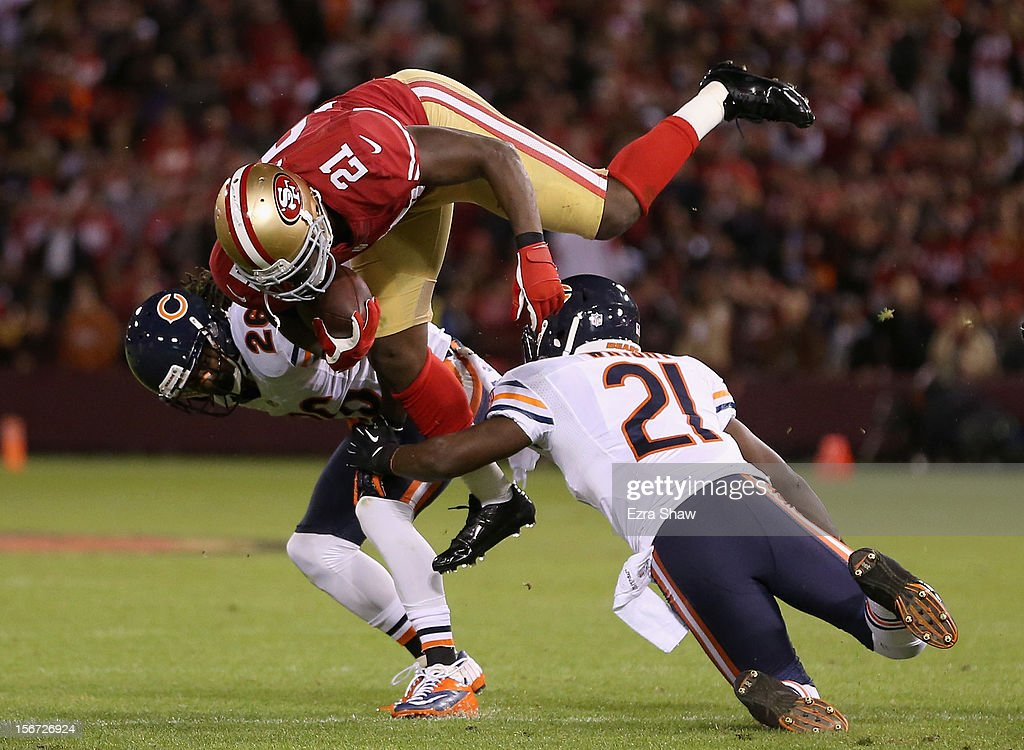 Frank Gore #21 of the San Francisco 49ers tries to jump over Major Wright #21 and Tim Jennings #26 of the Chicago Bears at Candlestick Park on November 19, 2012 in San Francisco, California.