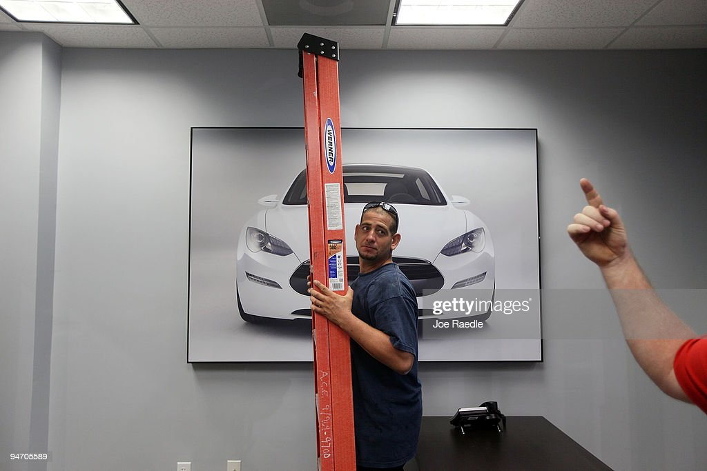Frank Jimenez carries a ladder as he helps put finishing touches on the showroom at the Tesla Motors first South Florida location on December 17, 2009 in Dania Beach, Florida. Tesla produces high-performance electric vehicles with a fully electric power train.