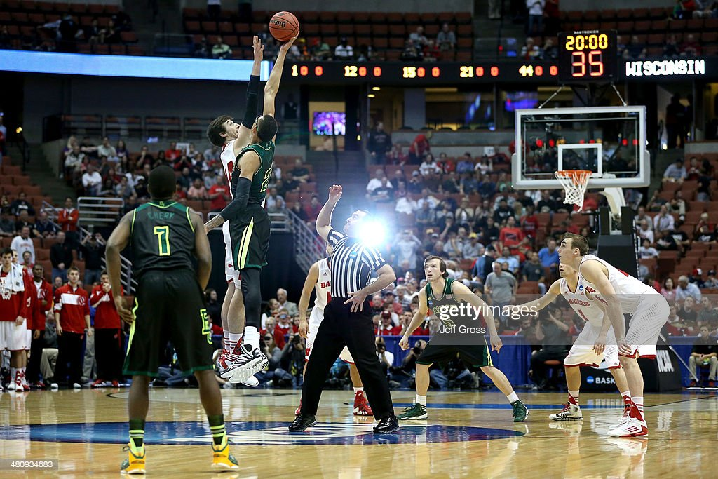 Frank Kaminsky of the Wisconsin Badgers and Isaiah Austin of the Baylor Bears go after the opening jump ball to start the regional semifinal of the...