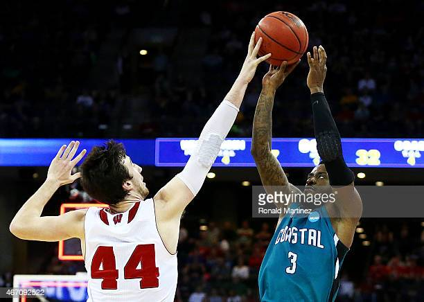 Frank Kaminsky of the Wisconsin Badgers blocks a shot by Josh Cameron of the Coastal Carolina Chanticleers in the first half during the second round...