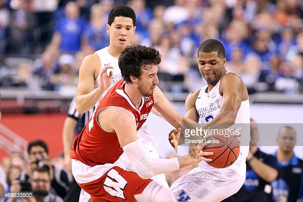 Frank Kaminsky of the Wisconsin Badgers handles the ball against Devin Booker and Aaron Harrison of the Kentucky Wildcats in the first half during...