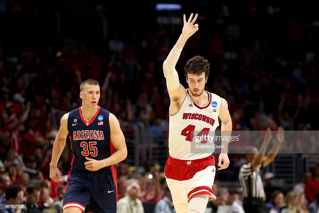 <a gi-track='captionPersonalityLinkClicked' href=/galleries/search?phrase=Frank+Kaminsky&family=editorial&specificpeople=8685398 ng-click='$event.stopPropagation()'>Frank Kaminsky</a> #44 of the Wisconsin Badgers reacts alongside <a gi-track='captionPersonalityLinkClicked' href=/galleries/search?phrase=Kaleb+Tarczewski&family=editorial&specificpeople=8047518 ng-click='$event.stopPropagation()'>Kaleb Tarczewski</a> #35 of the Arizona Wildcats after Kaminsky makes a three-pointer in the second half during the West Regional Final of the 2015 NCAA Men's Basketball Tournament at Staples Center on March 28, 2015 in Los Angeles, California.