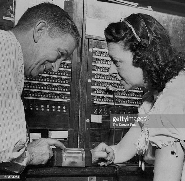 6261949 Frank L Wallace chief engineer for the Cosmopolitan hotel shows Miss Irma DeDisre switchboard operator the workings of the motel's new fire...