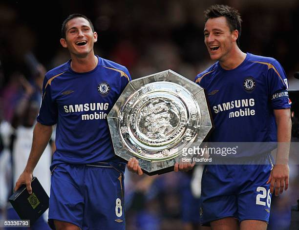 Frank Lampard and John Terry of Chelsea share a joke as they celebrate with the trophy following the FA Community Shield match between Arsenal and...