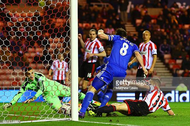 Frank Lampard of Chelsea and Lee Cattermole of Sunderland slide in to score the opening goal during the Capital One Cup QuarterFinal match between...