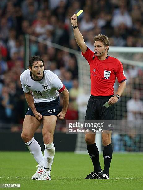 Frank Lampard of England is shown a yellow card by referee Felix Brych during the International Friendly match between England and Scotland at...
