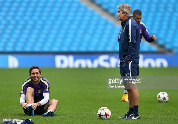 Frank Lampard of Manchester City and Manuel Pellegrini the manager of Manchester City chat during a training session at the Etihad Stadium on...