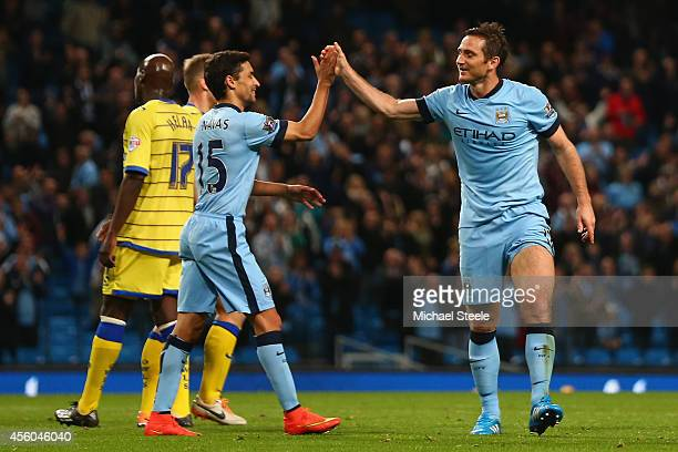 Frank Lampard of Manchester City celebrates with Jesus Navas after scoring the seventh goal during the Capital One Cup Third Round match between...