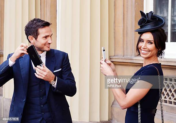 Frank Lampard poses with partner Christine Bleakley as he holds his Officer of Order of the British Empire medal after it was presented to him by the...