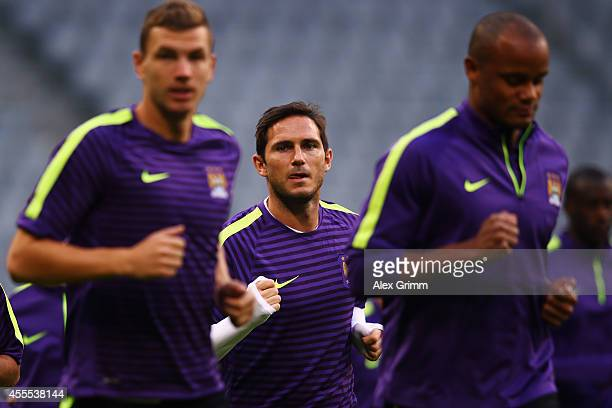 Frank Lampard warms up with Edin Dzeko and Vincent Company during the Manchester City training session ahead of their UEFA Champions League Group E...