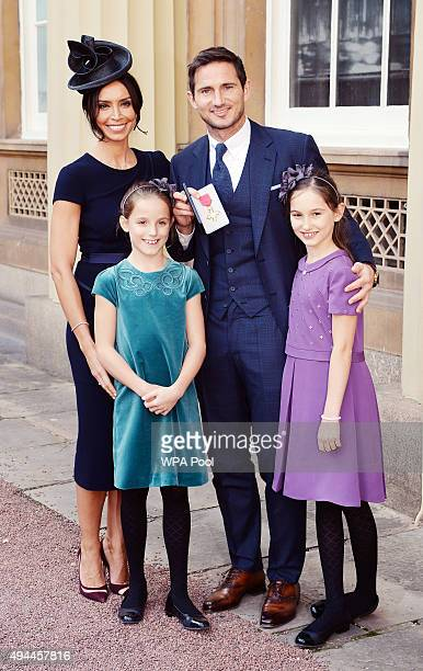 Frank Lampard with partner Christine Bleakley and his daughters Isla and Luna as he holds his Officer of Order of the British Empire medal after it...