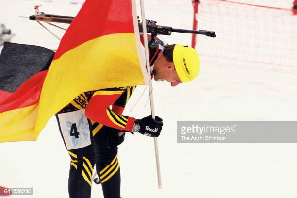 Frank Luck of Germany holds the national flag reacts after crossing the finish line to win the gold medal in the Biathlon Men's 4x75km Relay during...