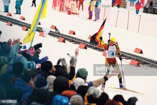 Frank Luck of Germany waves the national flag as he crosses the finish line to win the gold medal in the Biathlon Men's 4x75km Relay during day...