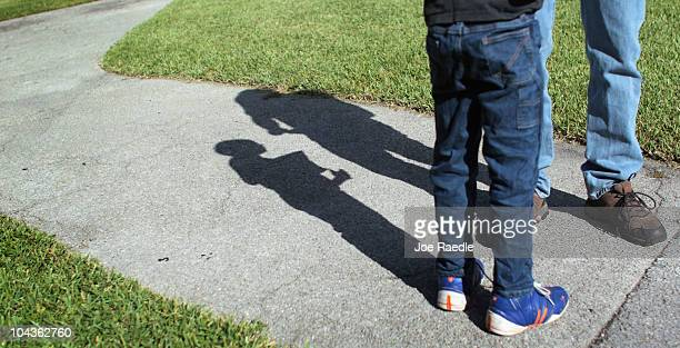 Frank Martin Gill casts a shadow on the ground as he talks with his sixyearold foster son known as NRG after the Third District Court of Appeal in...
