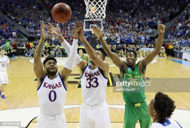 Frank Mason III and Landen Lucas of the Kansas Jayhawks battle for a rebound with Kavell BigbyWilliams of the Oregon Ducks in the first half during...