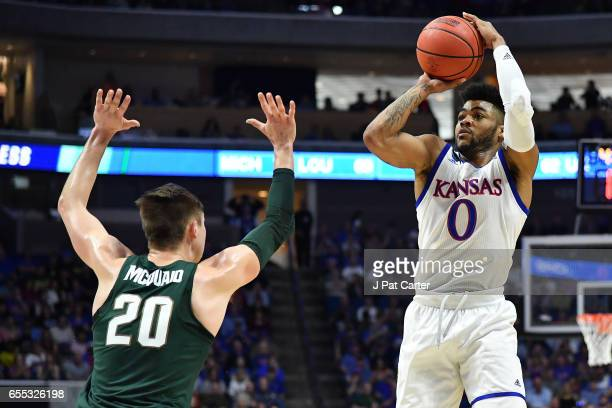 Frank Mason III of the Kansas Jayhawks attempts a shot defended by Matt McQuaid of the Michigan State Spartans during the second round of the 2017...