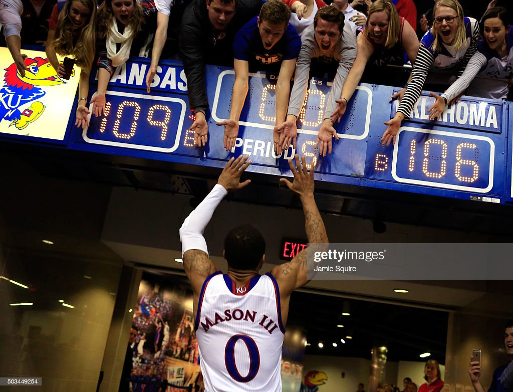 Frank Mason III of the Kansas Jayhawks celebrates with fans as he leaves the court after the Jayhawks defeated the Oklahoma Sooners 109106 in triple...