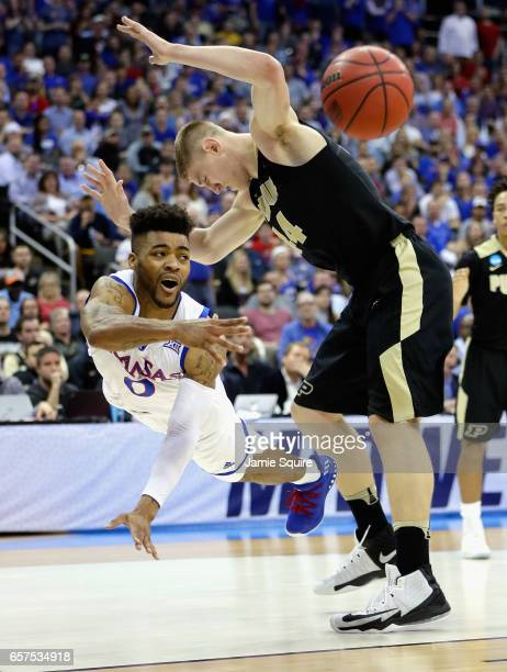 Frank Mason III of the Kansas Jayhawks falls as he passes the ball against Isaac Haas of the Purdue Boilermakers in the first half during the 2017...