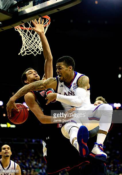 Frank Mason III of the Kansas Jayhawks passes around Brekkott Chapman of the Utah Utes to Perry Ellis during the game at the Sprint Center on...