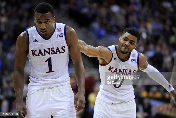 Frank Mason III slaps Wayne Selden Jr #1 of the Kansas Jayhawks on the back as Selden goes to the free throw line against the West Virginia...