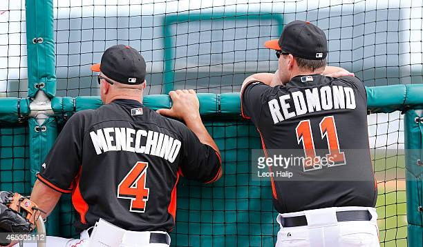 Frank Menechino and manager Mike Redmond of the Miami Marlins watch batting practice prior to the start of the spring training game against the St...