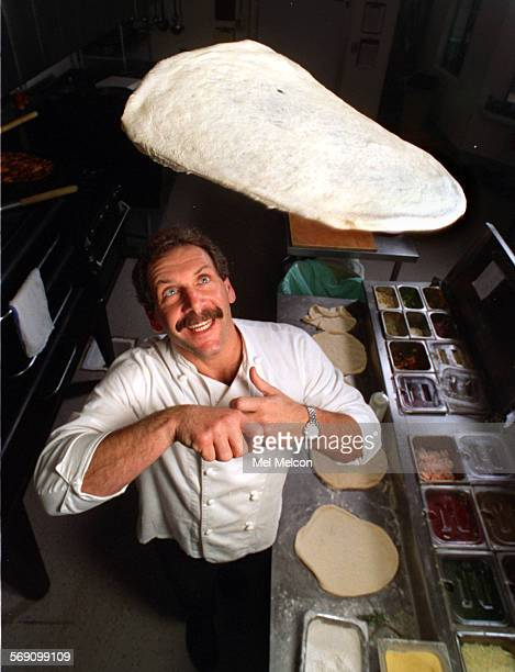 Frank Miller owner chef at Cutting Edge Pizza Factory in Ventura tosses olive oil honey pizza dough inside kitchen area where pizzas are prepared
