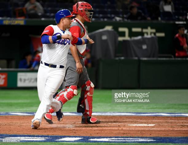 Frank Morejon of Cuba crosses the home plate following a threebase hit by Roel Santos at the 4th inning of the World Baseball Classic Pool B first...
