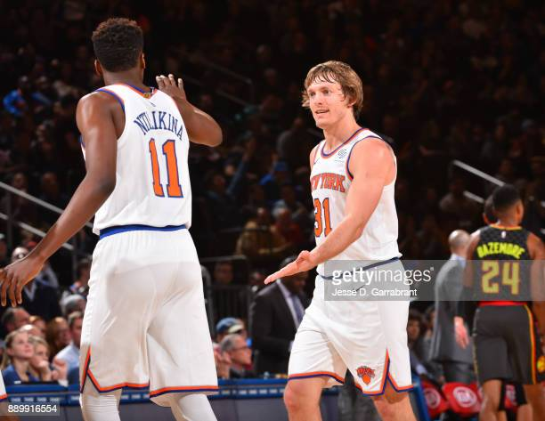 Frank Ntilikina and Ron Baker of the New York Knicks shake hands against the Atlanta Hawks at Madison Square Garden on December 10 2017 in New York...
