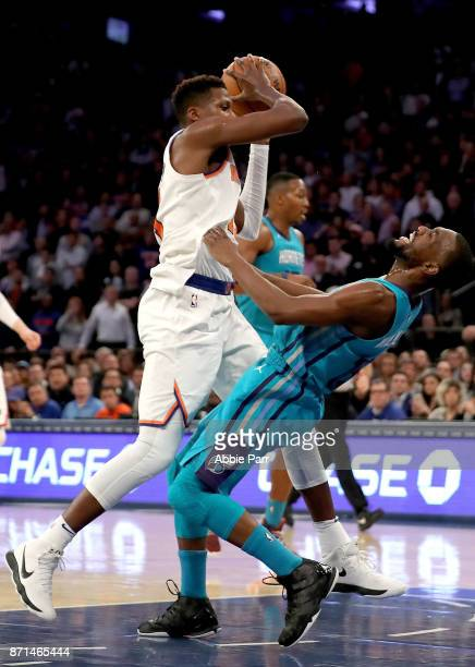Frank Ntilikina of the New York Knicks commits an offensive foul against Kemba Walker of the Charlotte Hornets in the fourth quarter during their...