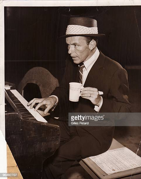 Frank Sinatra holding a paper mug and playing an organ in a recording studio c 1953 in the United States