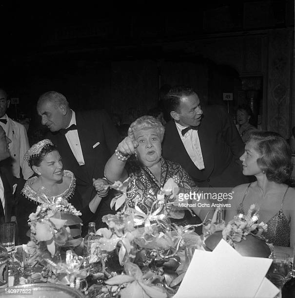 Frank Sinatra listens in as actress and singer Judy Garland comedienne Sophie Tucker and actress Lauren Bacall share a joke at the party celebrating...