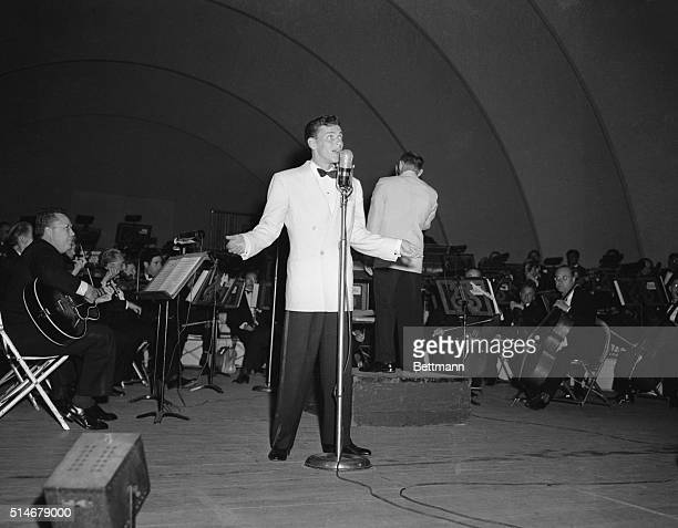 8/1943 Frank Sinatra performs at the Hollywood Bowl Here he stands full length crooning into a microphone wearing a white jacket and black pants SEE