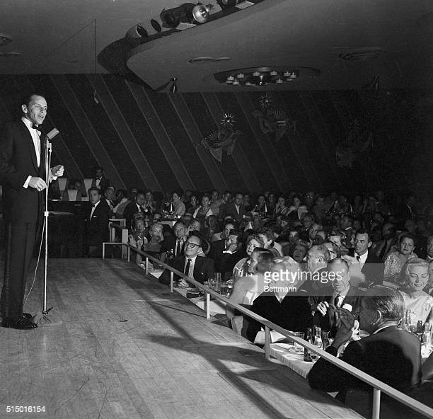 Frank Sinatra sings on the stage of the Sands Hotel At the tables in the front are Jack Benny several unidentified people Kim Novak Cole Porter and...
