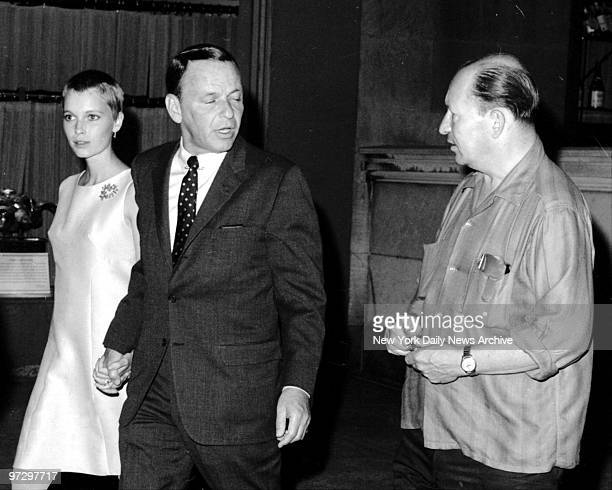 Frank Sinatra talks to a fan as he and wife Mia Farrow leave 21 Club