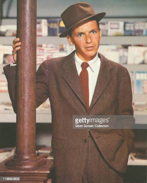 Frank Sinatra US singer and actor dressed in a brown jacket brown fedora white shirt and a redandblack tie leaning against a lamppost circa 1955