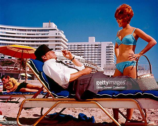 Frank Sinatra US singer and actor laying on a sun lounger on a beach with Jill St John US actress wearing a blue bikini in a publicity still issued...