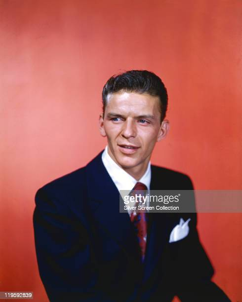Frank Sinatra US singer and actor wearing a dark blue jacket a white shirt and a redandblue tie in a studio portrait against a red background circa...