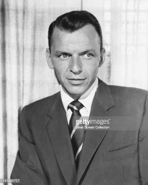 Frank Sinatra US singer and actor wearing a dark suit with a white shirt and striped tie in a studio portrait circa 1955