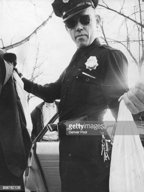 Frank Smith shows coats worn by stickups and pillow slip filled with stolen money Patrolman Arthur T Arita shows three heavy caliber weapons taken...