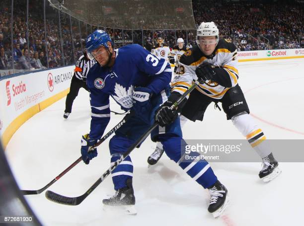 Frank Vatrano of the Boston Bruins checks Josh Leivo of the Toronto Maple Leafs during the second period at the Air Canada Centre on November 10 2017...
