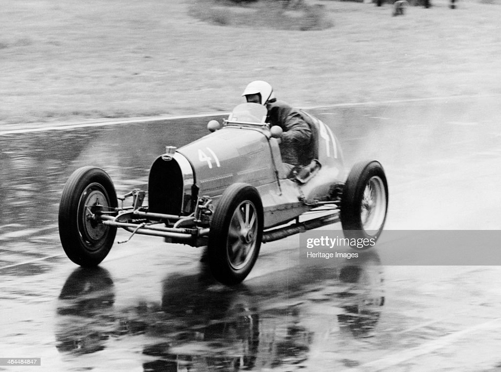 Frank Wall driving a Bugatti Type 35B 1926 Driving on a wet racetrack with spray coming off the back wheels