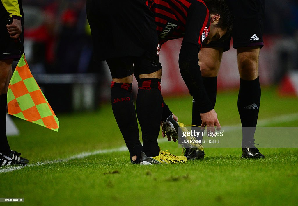 Frankfurt's Croation striker Serjan Lakic puts his shoe back on afte it came off during the German first division Bundesliga football match Hamburg SV vs Eintracht Frankfurt in Hamburg, northern Germany on February 2, 2013. AFP PHOTO / JOHANNES EISELE