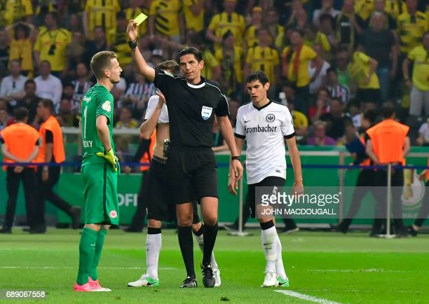 Frankfurt's Finnish goalkeeper Lukas Hradecky is shown a yellow card by the referee Deniz Aytekin during the German Cup final football match...