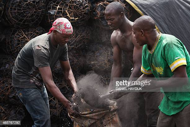Franki Nnko Gordon William and Japhet Edward gather char powder from a charcoal depot in Dar es Salaam on March 10 2015 ARTI Energy is a Tanzanian...