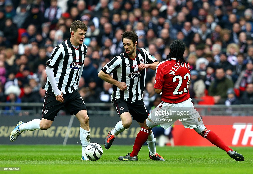 Frankie Artus of Grimsby Town is tackled by Chris Westwood of Wrexham during the FA Trophy Final between Wrexham and Grimsby Town at Wembley Stadium on March 24, 2013 in London, England.