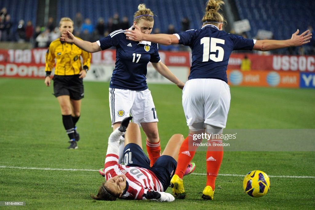 Frankie Brown #17 and Joelle Murray #15 of the Scotland Women's National Team stand over <a gi-track='captionPersonalityLinkClicked' href=/galleries/search?phrase=Carli+Lloyd&family=editorial&specificpeople=736799 ng-click='$event.stopPropagation()'>Carli Lloyd</a> #10 of the U.S. Women's National Team at LP Field on February 13, 2013 in Nashville, Tennessee.