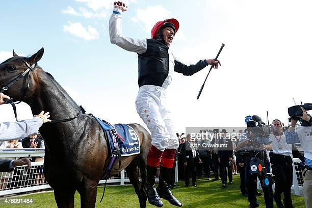 Frankie Dettori leaps from Golden Horn after winning The Investec Derby at Epsom racecourse on June 06 2015 in Epsom England