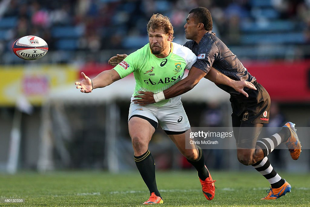 Frankie Horne #3 of South Africa gets a pass away under pressure from Apisai Domolailai #3 of Fiji during the Cup Final at the Tokyo Sevens, in the six round of the HSBC Sevens World Series at the Prince Chichibu Memorial Ground on March 23, 2014 in Tokyo, Japan.