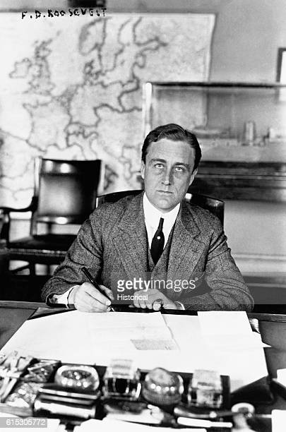 Franklin D Roosevelt signs papers in his office during his service as assistant secretary to the United States Navy